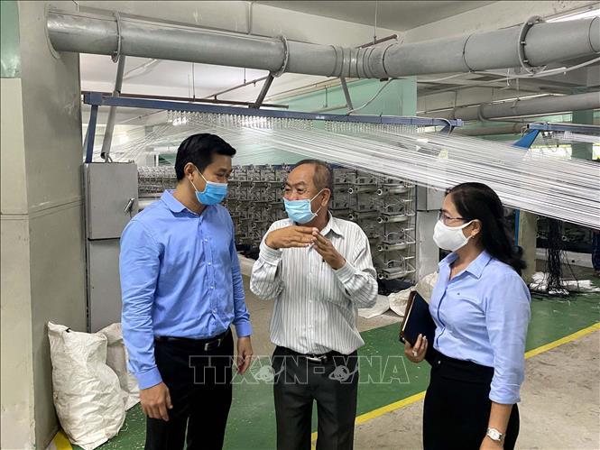 Ông Hứa Quốc Hưng, Trưởng Ban Quản lý các Khu chế xuất, Khu công nghiệp Thành phố Hồ Chí Minh cùng đoàn đại biểu với lãnh đạo Công ty trách nhiệm hữu hạn In và sản xuất bao bì Đức Mỹ, ở khu công nghiệp Hiệp Phước. Ảnh: Thanh Vũ - TTXVN