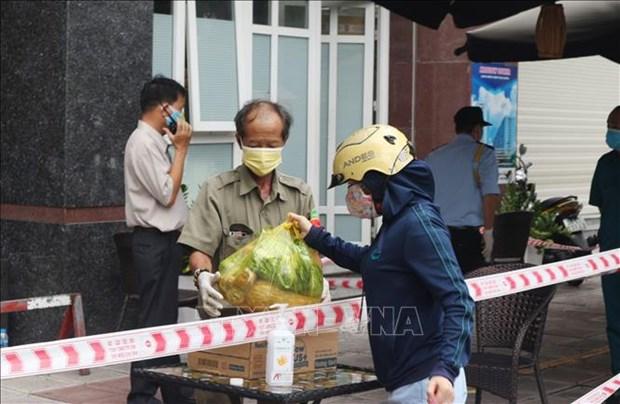 Trước diễn biến mới của dịch Covid-19, từ ngày 28/01/2021, Thành phố Hồ Chí Minh chính thức tái kích hoạt hệ thống phòng, chống dịch bệnh tại các cơ quan, đơn vị và địa phương trên địa bàn. Trong ảnh (tư liệu): Lực lượng bảo vệ hỗ trợ người dân vận chuyển