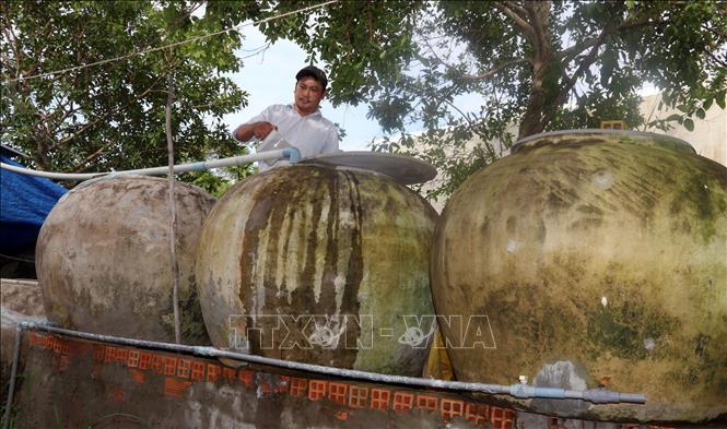 Tranh thủ vào mùa mưa, người dân sinh sống ven biển An Biên tận dụng lu để chứa nước sử dụng. Ảnh: Lê Sen - TTXVN