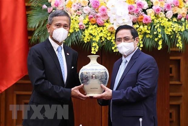越南政府总理范明政会见新加坡外长 hinh anh 1